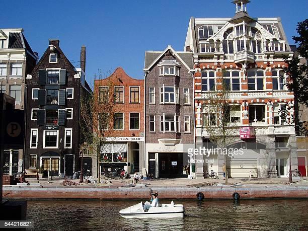 Touristen fahren mit einem Tretboot auf einer Gracht an schoenen alten Haeusern vorbei