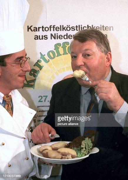 Niedersachsens Landwirtschaftsminister KarlHeinz Funke probiert am in Hannover frische Pellkartoffeln die ihm von Michael Schlüter zur Eröffnung der...