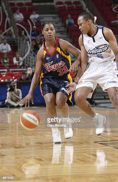 Niele Ivey of the Indiana Fever is defended by Elaine Powell of the Orlando Miracle in the game on June 11 2002 at TD Waterhouse Centre in Orlando...