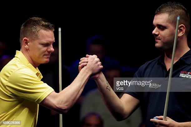 Niels Feijen of Netherlands shakes hands with Daniele Corrieri of Italy on day one of the Partypoker World Pool Masters 2014 at Portland Centre on...