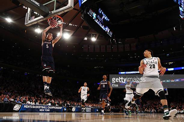 Niels Giffey of the Connecticut Huskies dunks the ball in the second half as Travis Trice of the Michigan State Spartans looks on during the East...