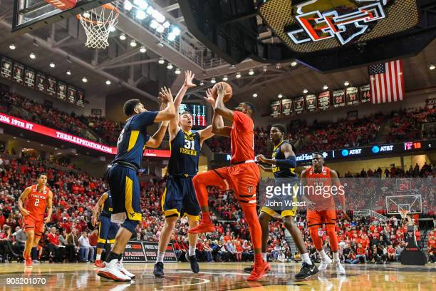 Niem Stevenson of the Texas Tech Red Raiders goes to the basket against Esa Ahmad of the West Virginia Mountaineers and Logan Routt of the West...