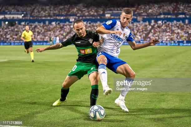 Nieto of Zaragoza competes for the ball with Nino of Elche CF during the La Liga Smartbank match between Zaragoza and Elche CF at La Romareda on...