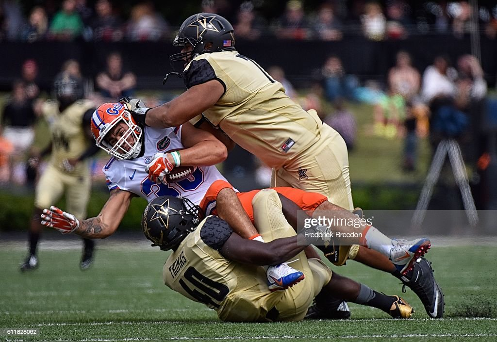 Nifae Lealao #77 and Ja'karri Thomas #40 of the Vanderbilt Commodores tackle DeAndred Goolsby #83 of the Florida Gators during the first half at Vanderbilt Stadium on October 1, 2016 in Nashville, Tennessee.