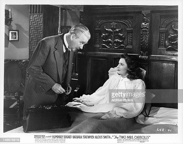 Nigel Bruce standing over Barbara Stanwyck in bed a scene from the film 'The Two Mrs Carrolls' 1947