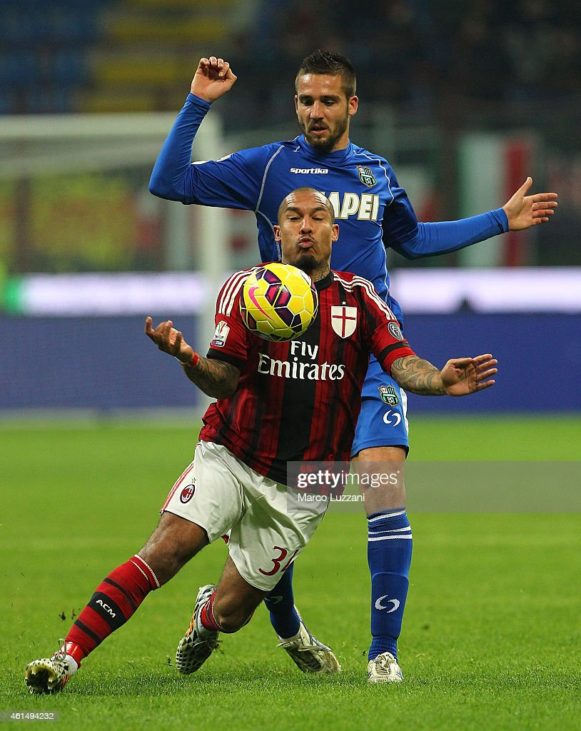 Nigel De Jong of AC Milan competes for the ball with Leonardo Pavoletti (back) of US Sassuolo Calcio during the TIM Cup match between AC Milan and US Sassuolo Calcio at Stadio Giuseppe Meazza on January 13, 2015 in Milan, Italy.