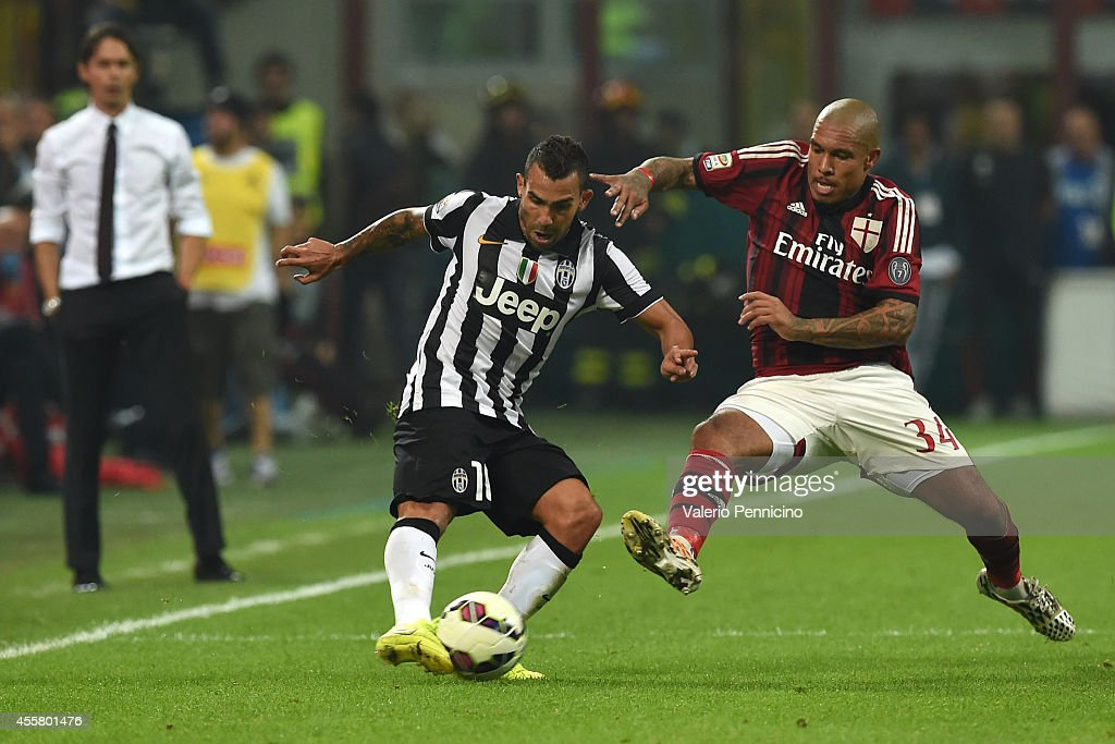 Nigel De Jong (R) of AC Milan tackles Carlos Tevez of Juventus FC during the Serie A match between AC Milan and Juventus FC at Stadio Giuseppe Meazza on September 20, 2014 in Milan, Italy.
