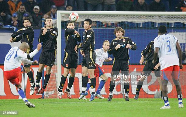 Nigel de Jong of Hamburg takes a free kick and the team of Rostock jump in the wall during the Bundesliga match between Hamburger SV and Energie...