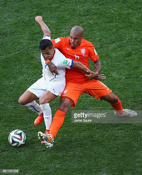 Nigel de Jong of the Netherlands and Alexis Sanchez of Chile battle for the ball during the 2014 FIFA World Cup Brazil Group B match between the...
