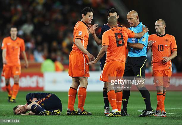 Nigel De Jong of the Netherlands appeals to Referee Howard Webb as he receives a yellow card for a kick in the chest on Xabi Alonso of Spain during...