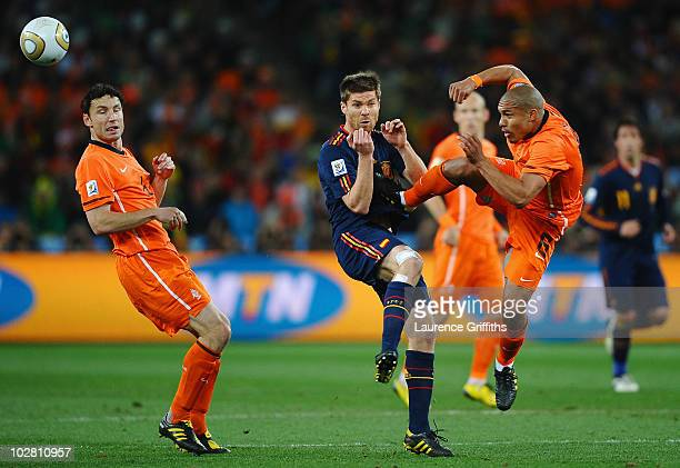 Nigel De Jong of the Netherlands tackles Xabi Alonso of Spain with a kick in the chest during the 2010 FIFA World Cup South Africa Final match...