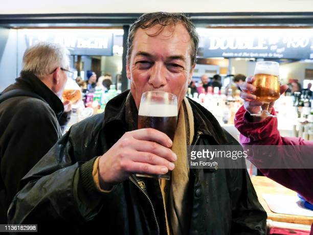 Nigel Farage enjoys a pint with fellow walkers as they arrive at the end of the first leg of the March to Leave campaign on March 16 2019 in...
