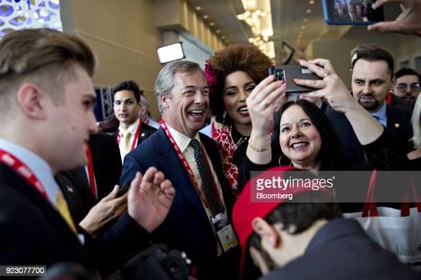 Nigel Farage former leader of the UK Independence Party center left takes a selfie photograph with attendees at the Conservative Political Action...