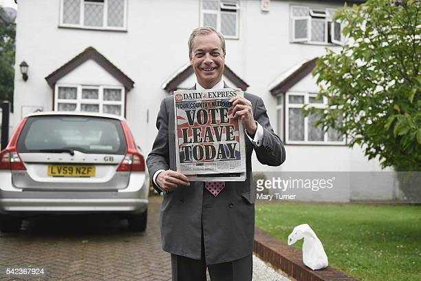 Nigel Farage leader of UKIP and Vote Leave campaigner holds up the 'Daily Express' as he returns to his home after buying newspapers of the United...
