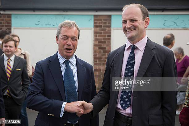 Nigel Farage the Leader of the UK Independence Party and Douglas Carswell MP prepare to walk through ClactononSea the day after Mr Carswell announced...