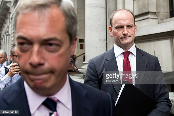 Nigel Farage the Leader of the UK Independence Party listens as Member of Parliament Douglas Carswell is interviewed in Westminster after announcing...