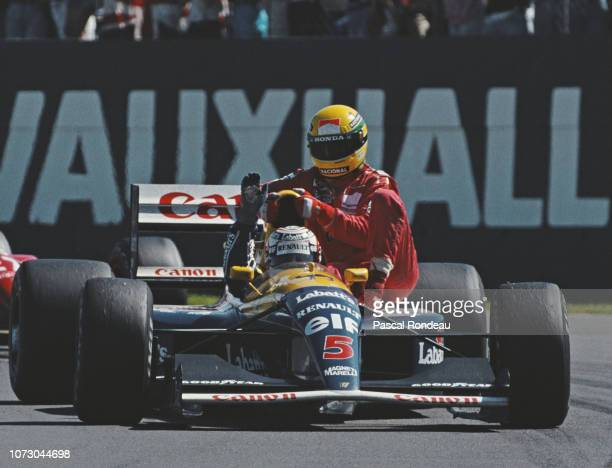 Nigel Mansell driving the Canon Williams Renault Williams FW14 Renault V10 gives Ayrton Senna a ride back to the pits after he had run out of fuel...