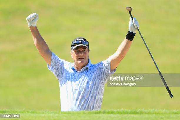 Nigel Mansell former F1 World Champion celebrates after holing his second shot for an eagle on the first hole during the Celebrity Golf Classic at...