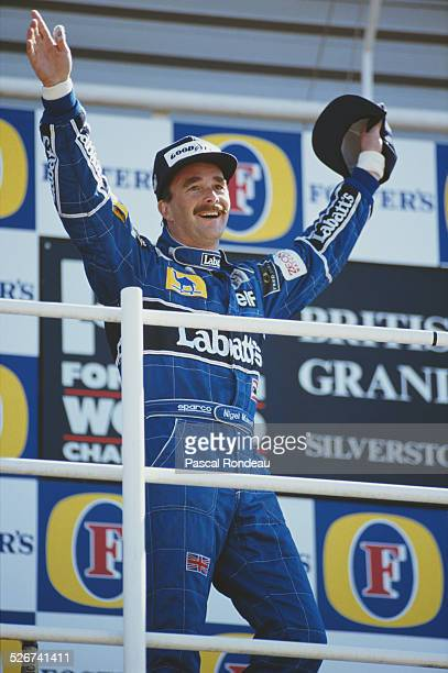 Nigel Mansell of Great Britain driver of the Canon Williams Renault Williams FW14 Renault RS3C V10 celebrates winning the British Grand Prix on 14th...