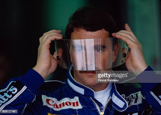 Nigel Mansell of Great Britain, driver of the Canon Williams Renault Williams FW14 Renault RS3C V10 looks through his visor before the the Canadian...