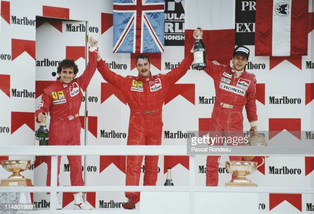 Nigel Mansell of Great Britain driver of the Scuderia Ferrari SpA Ferrari F1902 Ferrari V12 celebrates with second placed team mate Alain Prost and...