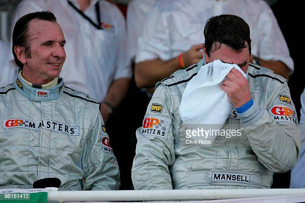 Nigel Mansell of Great Britain wipes away his tears on the podium as Emerson Fittipaldi looks on after the Grand Prix Masters race at the Kyalami...