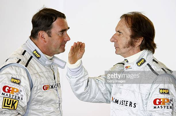 Nigel Mansell speaks to Emerson Fittipaldi during testing for the GP Masters of Great Britain at Silverstone circuit on August 10 in Silverstone...