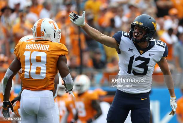 Nigel Warrior of the Tennessee Volunteers watches as David Sills V of the West Virginia Mountaineers reacts after a catch during their game at Bank...
