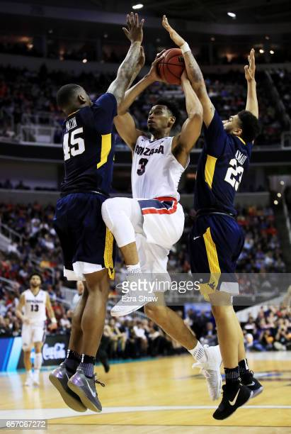 Nigel WilliamsGoss of the Gonzaga Bulldogs goes up against Elijah Macon and Esa Ahmad of the West Virginia Mountaineers in the second half during the...