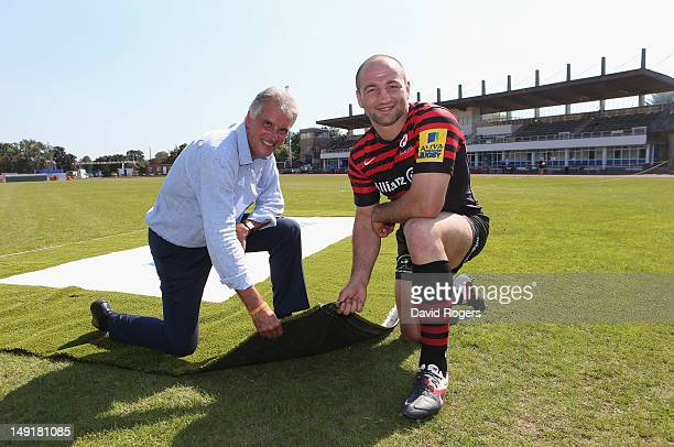 Nigel Wray owner of Saracens holds up the artificial turf which Sarries will play on with club captain Steve Borthwick during the press conference...