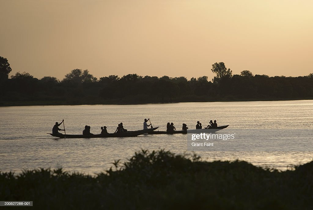 Niger River Children In Canoes Paddling Down The Side View