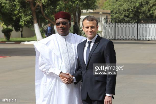 Niger president Mahamadou Issoufou shakes hands with French president Emmanuel Macron during a military welcome ceremony at the Presidential palace...