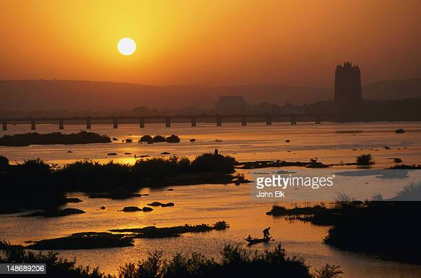 niger river at sunset, with bceao bank in background. - bamako stock pictures, royalty-free photos & images
