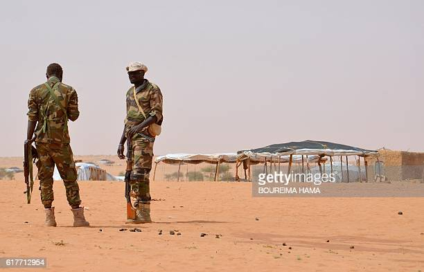 Niger soldiers stand guard during a visit by the Interior Minister Mohamed Bazoum on October 21 2016 to the in Tazalit United Nations refugee camp in...