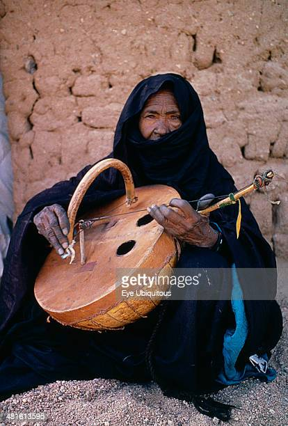 Niger, Tribal Music, Tuareg woman playing an Imzad. Traditional instrument consisting of a goatskin covered gourd or wooden resonator played with a...