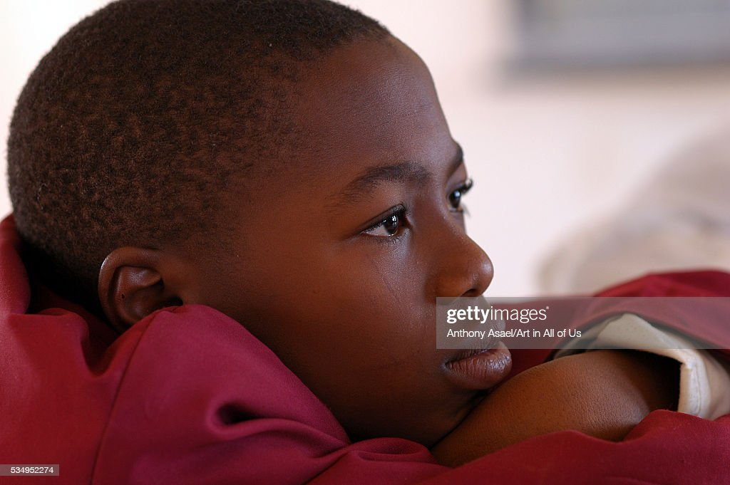 Nigeria, Jos, Portrait of a schoolboy wearing a purple vest, looking thoughtfully in front of him : News Photo