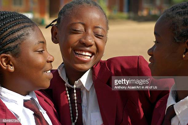 Nigeria, Jos, Portrait of schoolgirls in their purple uniform, smiling and laughing, embracing each other