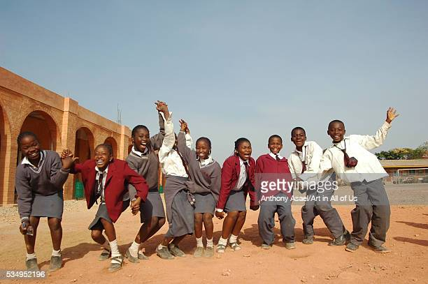 Nigeria, Jos, Schoolboys and schoolgirls, holding each others hand, and standing in line, smiling and waving