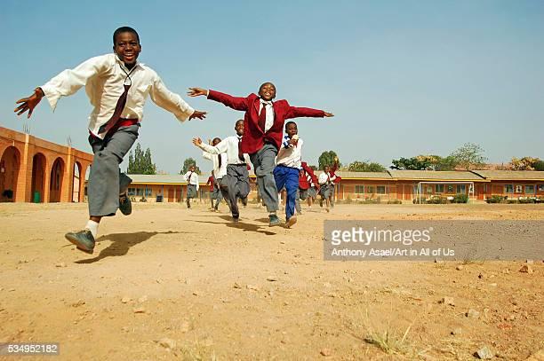 Nigeria Jos Schoolboys and schoolgirls in their purple and blue school uniform running alltogether on a field