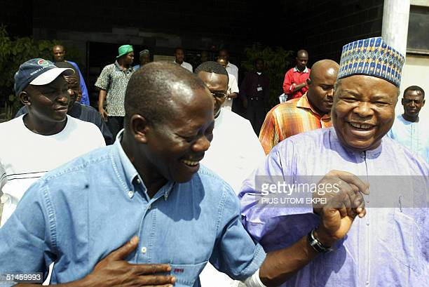 Nigeria Labour Congress President Adams Oshiomhole and Deputy Senate President Ibrahim Mantu hold hands after a meeting between senate...
