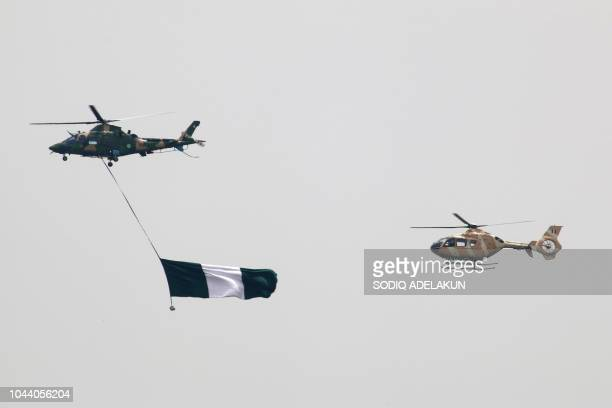 Nigerian Air Force helicopters perfom with the flag of Nigeria during a parade marking the country's 58th anniversary of independence on October 1 on...