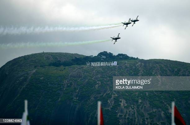 Nigerian Airforce Planes fly past a Nigerian 60th anniversary banner at the Aso-Rock in Abuja, Nigeria during the countrys 60th Independence...