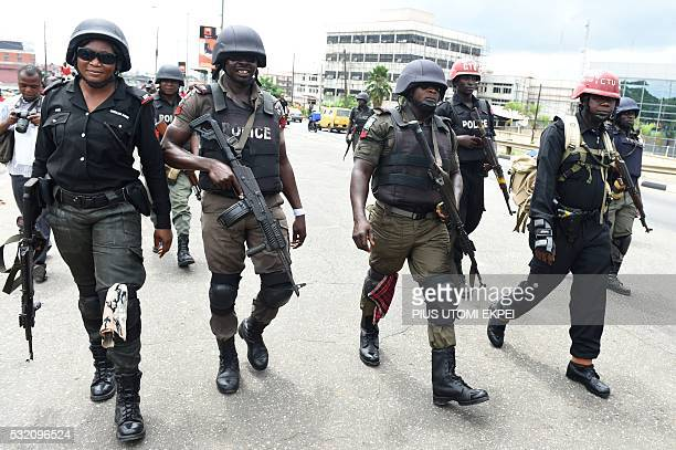 Nigerian Anti riots policemen walks to stop demonstrators during a protest demanding that the government reinstate prices of fuel at 8650 naira per...