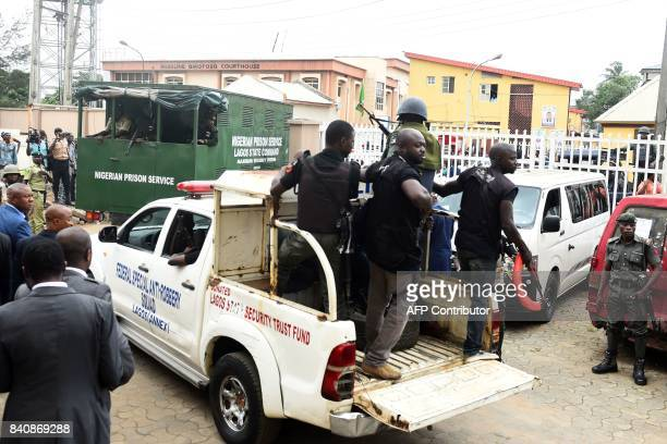 Nigerian antriot police officers escort a suspected kidnap kingpin to prison after he was arraigned at the Lagos State High Court on August 30 2017...
