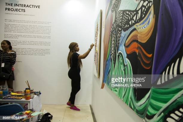 Nigerian artist Queen Nwaneri paints during the Nigeria annual Art X event in Lagos on November 4 2017 / AFP PHOTO / EMMANUEL AREWA