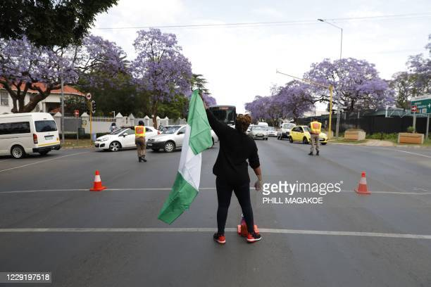 Nigerian based in South Africa waves the Nigerian national flag during a protest outside their embassy in Pretoria on October 21, 2020 in solidarity...