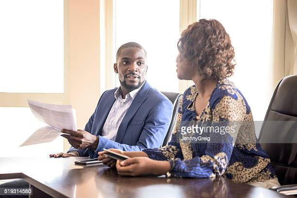 Nigerian business people in meeting with documents