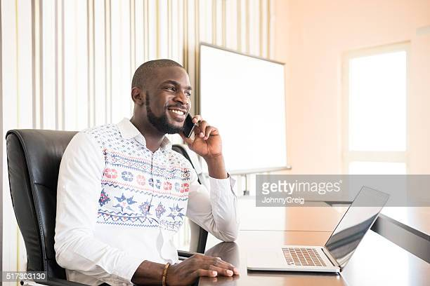 Nigerian businessman on cell phone modern office