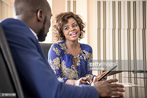 Nigerian businesswoman smiling at male colleague in meeting