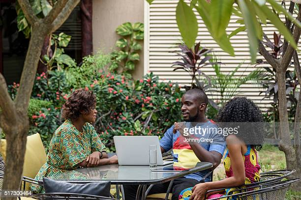 Nigerian colleagues with laptop talking in garden
